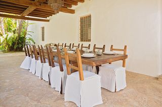 This gorgeous Ibiza finca is simply stunning. Country chic rustic dining table and chairs, linen seat covers - so romantic. True ibiza style