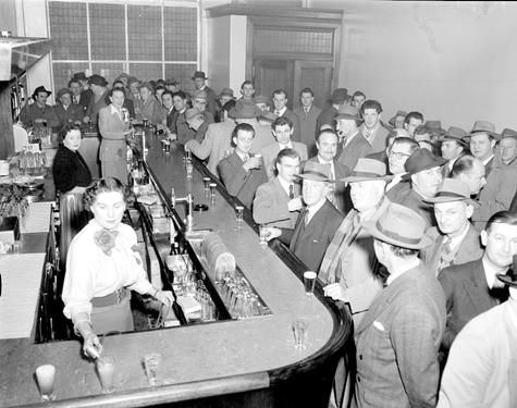 "Opening of the new bar at Hotel London, Elizabeth Street, Melbourne, 24 July 1953. The liquor licensing laws of the day obliged public bars to close at 6 pm The ensuing rush to the bar to line up drinks before closing time became known as the ""six o'clock swill""."