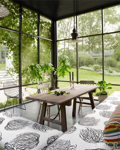 A screened porch with Hable Construction outdoor fabric, antique chairs and floors painted in Farrow & Ball's Studio Green.