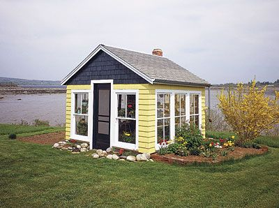 This garden house featuresa shingled roof, but the many windows on each wall make it a bright place for over-wintering tender plants and gr...