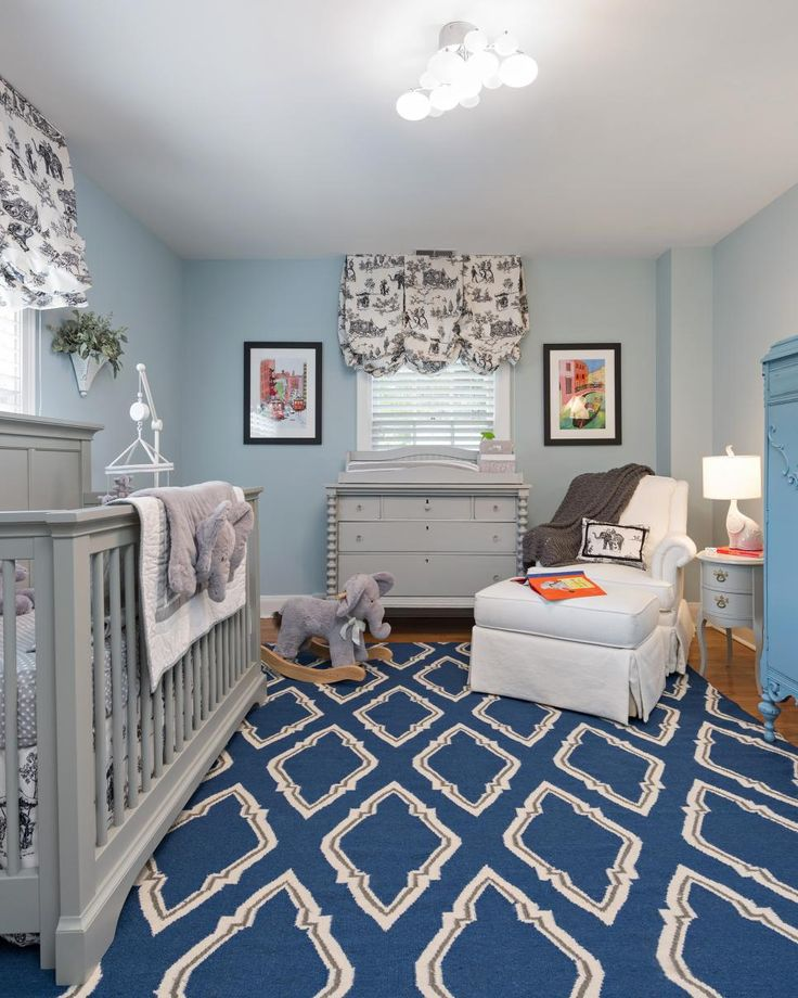 A dark blue diamond-patterned rug adds some interest to this light blue boy's nursery. A gray crib and changing table are chic additions to the elephant-themed space.