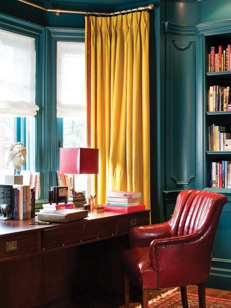 Colors and patterns happily commingle in a richly layered library. Vibrant linen curtains play off cerulean blue millwork, as does a red wing chair that interior designer Theresa Casey picked up in New York.