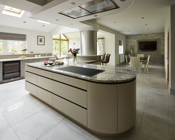 A curved island needn't mean wasted space - sleek handleless cupboards are the perfect way to maximise storage, as seen here in this Davonport kitchen featuring Miele appliances