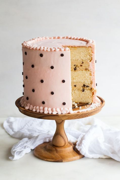 This fluffy white cake with cookie dough filling was inspired by the classic pairing that is Milk & Cookies. Smoothered in creamy frosting and dotted with mini