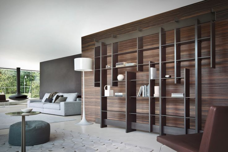 Horizontal and vertical lines follow each other in an apparently disordered pattern, creating a graphic image of great effect and elegance, matter that decomposes and enriches the bookcase by the use of diverse materials such as light and dark wood, with a wax finish, iron and oxidized brass.