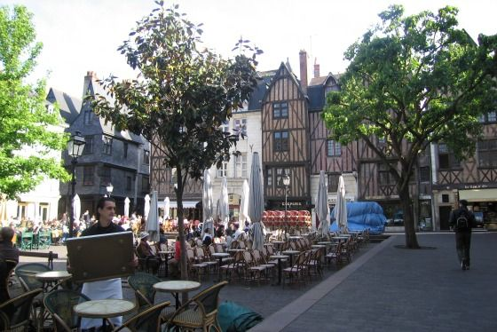 "Located in Tours, France, ""La Place Plumereau"" is a busy square filled with pubs and restaurants."