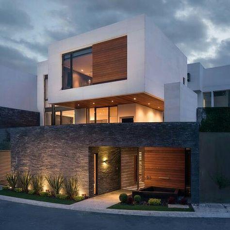 Fachada reta branca, com acabamento em madeira e vidro. Iluminação direta e indireta. Muro em pedra com portão.