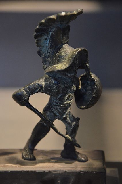 "A Hoplomachus (pl. hoplomachi) (Greek: ὁπλομάχος) (hoplon meaning ""shield"" in Greek) was a type of gladiator in ancient Rome, armed to resemble a Greek hoplite (soldier with heavy armor and helmet, a round shield, a spear and a sword). The hoplomachus would wear a bronze helmet, a manica on his right arm, loincloth (subligaculum), heavy padding on his legs, and a pair of high greaves reaching to mid-thigh. His weapons were the spear and a short sword."