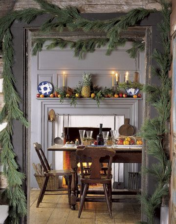 Garlands around the door frame beckon guests into the dining room. The theme is echoed within the room, above the fireplace, and on the fruit-dappled mantel.
