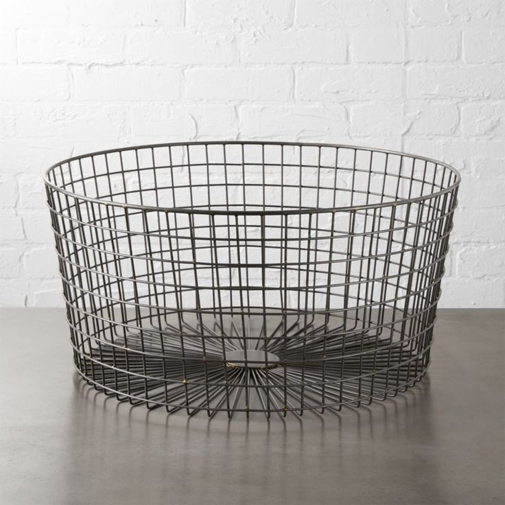 Shop gridlock large raw industrial basket.   Radial burst of iron wire cages clutter in an airy, freeform grid of mint or welded industrial.  Scaled low and broad, handcrafted baskets contain objects large and small, and tuck neatly under a coffee table.