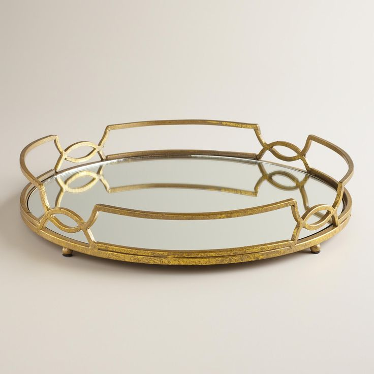 Crafted of metal and glass, our elegant Gold Mirrored Tabletop Tray features a footed base to place on tables, ottomans and other surfaces.