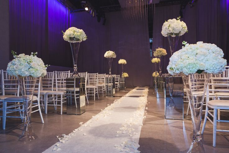 Ceremony - White aisle runner with ivory and blush rose petals on each side, Large vases with white Hydrangea's and white chivary chairs http://www.fusion-events.ca/