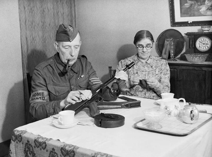 A sergeant in the Dorking Home Guard cleaning his Thompson submachine gun in his home Dorking southern England United Kingdom 1 December 1940.