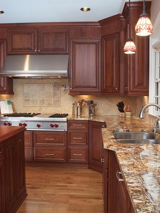 pictures of yellow kitchen with cherry cabinets and black counters  | Baltic Brown Kitchen with cherry cabinets and white appliances.