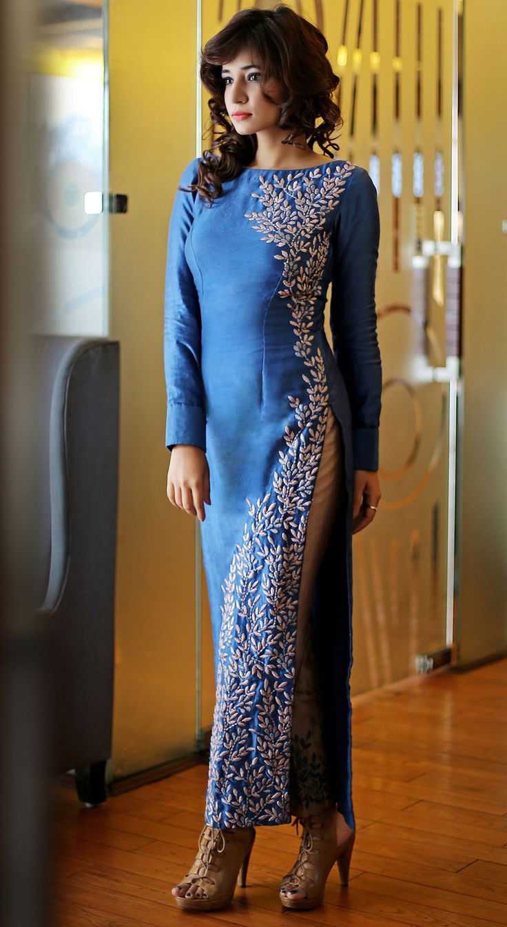 "an ankle length, sheath kurta with a pair of trousers, both made in Chanderi silk. In a ""true-blue"" color, the kurta has a lopsided embroidery in beige silk threads. The trousers are contrasting, having a beige base and true-blue embroidery."