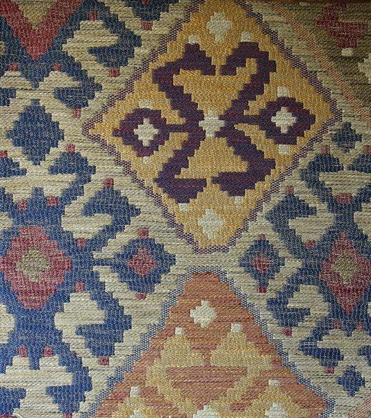 Kilim Upholstery Fabric Heavy weight upholstery fabric in the style of a turkish rug, in blue, yellow, red and beiges