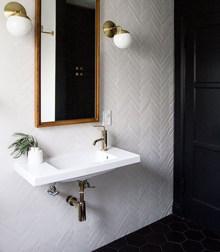 Walls Clad In A White Herringbone Tiles With A West Elm Floating Wood Wall  Mirror Illuminated By Cedar Moss Alto Sconces Over A White Porcelain Wall Mount  ...