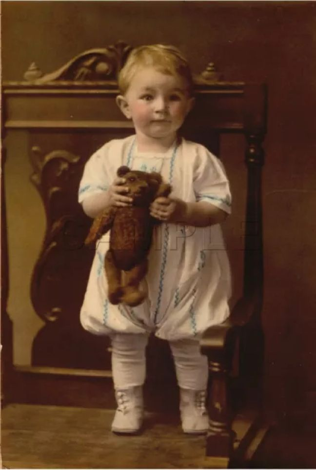 Antique photo of a  boy with his teddy bear.
