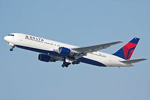 A side/underneath view of a 767-300ER in Delta Air Lines' white, blue and red color during climbout.  The main undercarriage doors are still retracting.