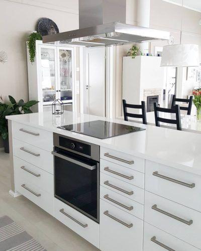 Valkoisen keittiösaarekkeen ääreltä avautuu näkymät ruokailutilaan ja olohuoneeseen