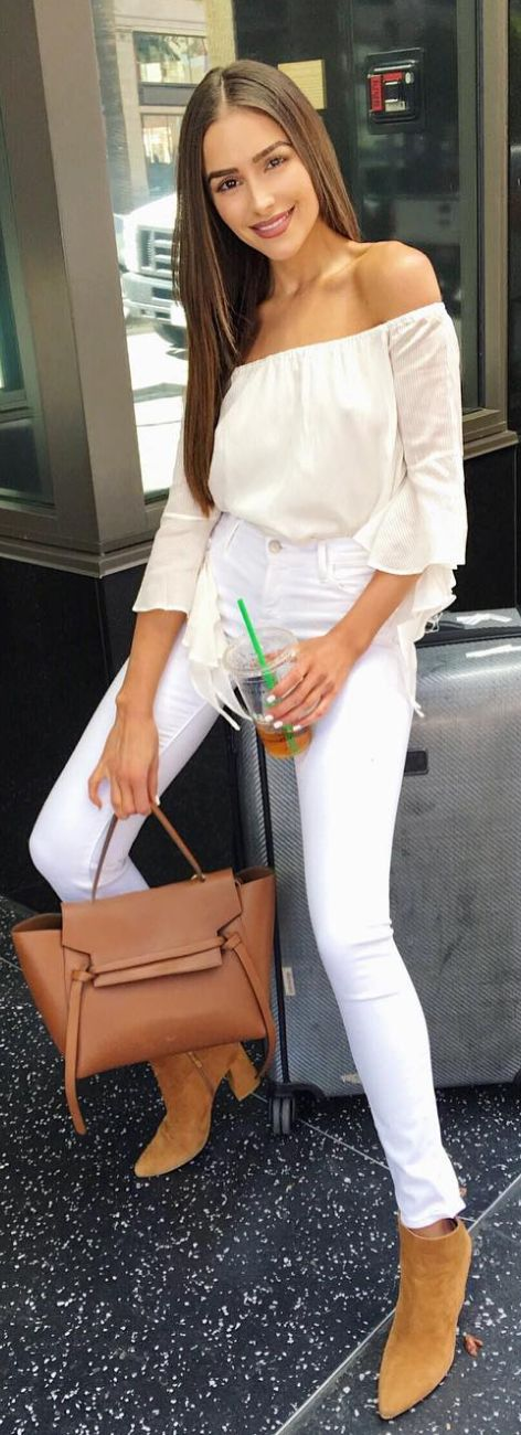 Who made Olivia Culpo's white off the shoulder top, skinny jeans, brown handbag, and suede ankle boots?