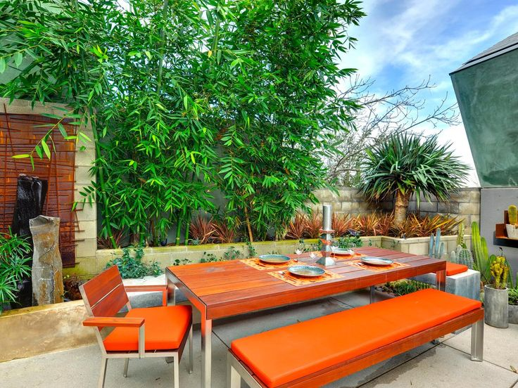 Eclectic Outdoor Terrace Great patio plantings, concrete scored and planters with cactus Orange cushions and gorgeous wood top table