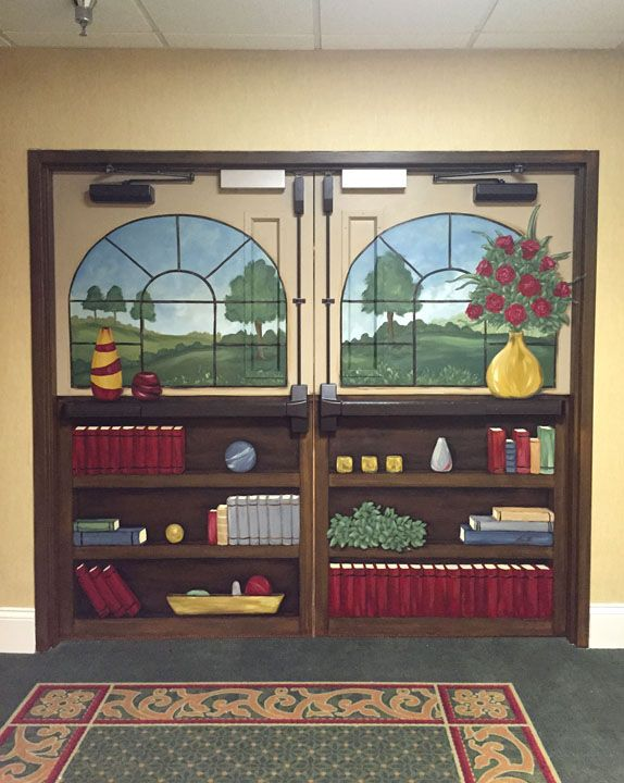 Bookshelf mural on the entrance to a Memory Care Unit at a local nursing home facility