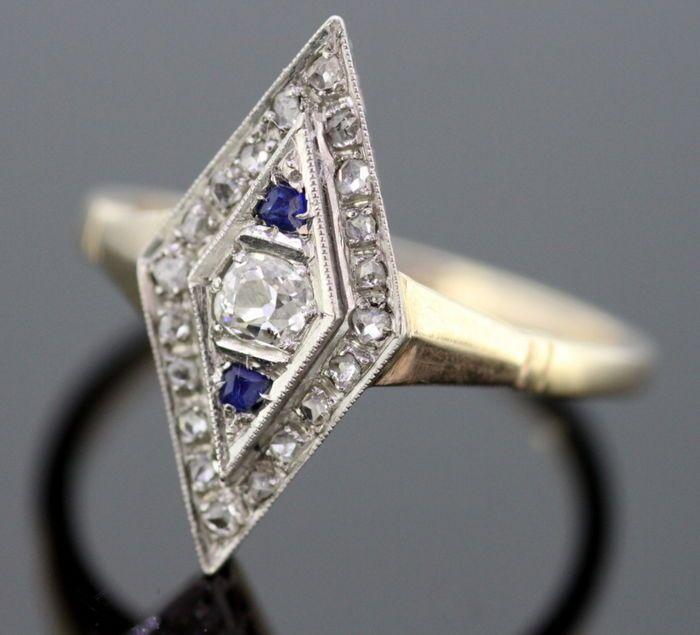 Art Deco 18K met Platinum rhombus damesring met diamanten (025 CT totaal) en blauwe saffier (004 CT totaal) ca. 1930  Art Deco 18K met Platinum rhombus damesring met diamanten (025 CT totaal) en blauwe saffier (004 CT totaal)Circa. 1930Afmeting-Grootte: (UK) = O (VS) = 7 1/2 (EU) = 55 1/4Gewicht: 3 gRing Bang breedte: 02 cmDe grootte van de ruit: 19 x 1 cmDiamanten-Knippen: rondeAantal diamanten: 21Carrat: 025 CT totaalDuidelijkheid: VS2Kleur: H / ikBlauwe saffier:Knippen: rondeCarrat: 004…