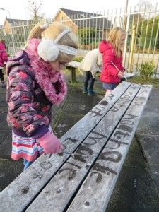 Kleuters verven letters op bevroren bankjes met warm water en een kwast, kleuteridee.nl