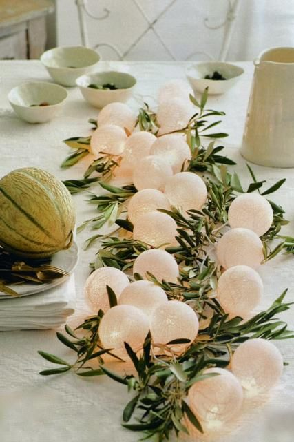 A string of white party lights intertwined with olive branches
