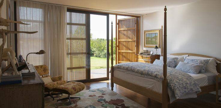 Quarto e decoração impecáveis em uma casa de campo paulista. Essa cama com balaustres é um convite sem recusas ao descanso. Poltrona: Charles Eames. Roupa de cama: Blue Gardenia.