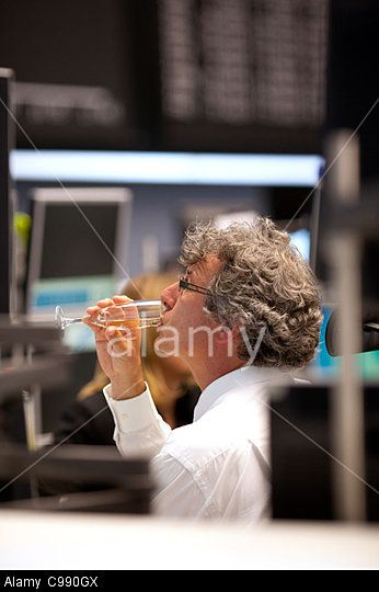 Trader drinking champagne on the Frankfurt Stock Exchange trading floor. © Jeff Gilbert / Alamy