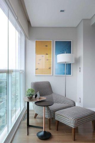 Varanda no mesmo nível da sala, poltrona com apoio de pés, mesas, iluminação embutida e abajur de piso, quadros pendurados na parede. Piso de madeira, cortina na varanda. Varanda decorada, decoração. Reforma e decoracao apto completo