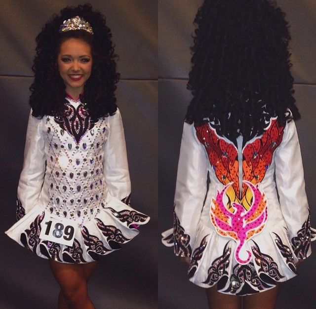 What a striking surprise! A fire breathing dragon is burning up the back of this simple white Irish dance dress.