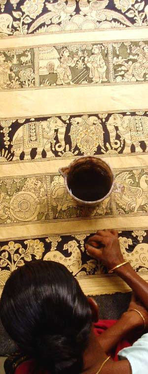 Woman using a kalam to draw on fabric. Photo from the Upasana Integral Design website.