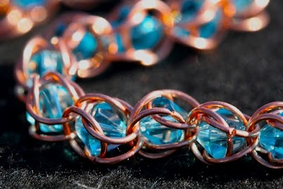 a bracelet made of 8mm blue bicone crystals with copper wire rings around them. … – zauberhafter Schmuck in Blau, Türkis und Gold – beautiful jewellry in blue, turquoise and gold