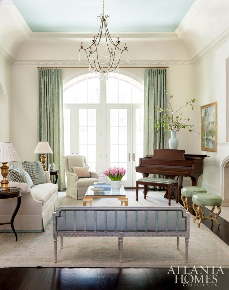 The formal living room is an exercise in both elegance and femininity with a mix of antiques and streamlined furnishings. The Louis XVI carved console, Baker striped sofa and 19th-century French trumeau imbue a sense of history, while the Anastasia Bench stools by Hickory Chair and painted ceiling (Rhine River by Benjamin Moore) add understated glamour.