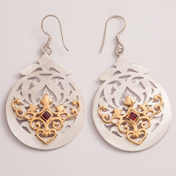 Stunning Shireen earrings with floral background in die cut satin finished silver. Handcrafted gold plated with garnet accent, these earrings designed by Puja Bhargava Kamath of Lai are part of the Malakeh collection, inspired by Islamic Central Asia.
