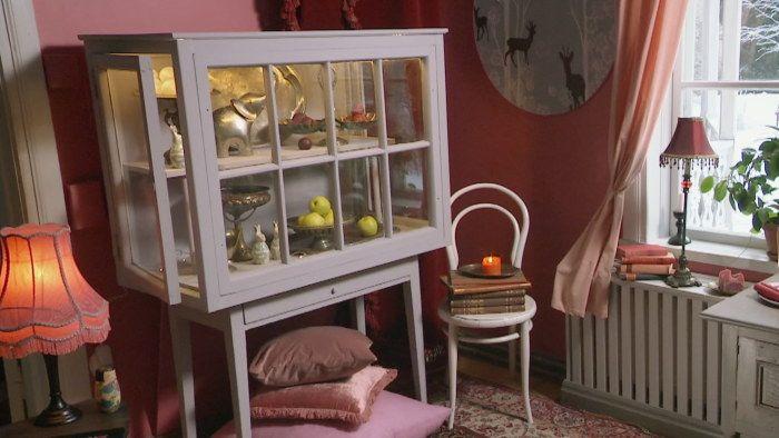 Ett gråmålat vitrinskåp som är gjort av gamla fönster. Skåpet står i ett vardagsrum med rosa väggar.