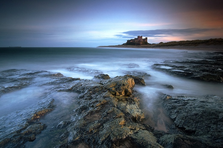 Late evening light catches the castle and some of the shore at Bamburgh, Northumbria, UK.