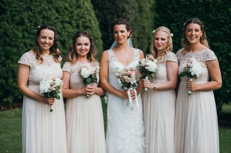 Full-length cream bridesmaids dresses with lace bodices and cap sleeves.