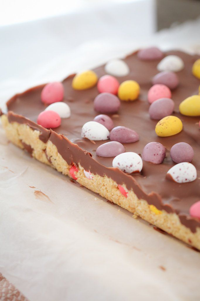 The easiest NO-BAKE EASTER EGG SLICE you'll ever make! A biscuit base filled with your favourite mini Easter eggs, topped with a chocolate layer and even more Easter eggs! #easter #egg #nobake #slice #thermomix #easy #conventiona #kidsrecipes #minieggs #chocolate #recipe