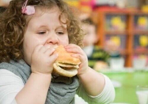 Pieni tyttö syö hampurilaista