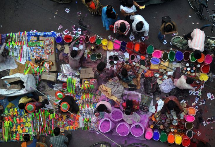 Indian vendors sell colored powder known as Gulal prior to the Holi festival in Siliguri on March 26, 2013