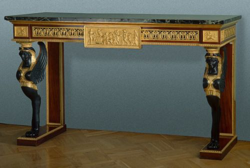 This console table has characteristics of the Empire era with it's rectangular shape and Egyptian themed ornamentation and front legs.