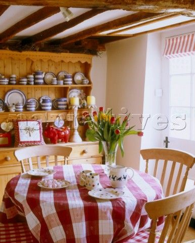 A Country Style Dining Room Circular Kitchen Table With Chequered Tablecloth And Wooden Chairs In