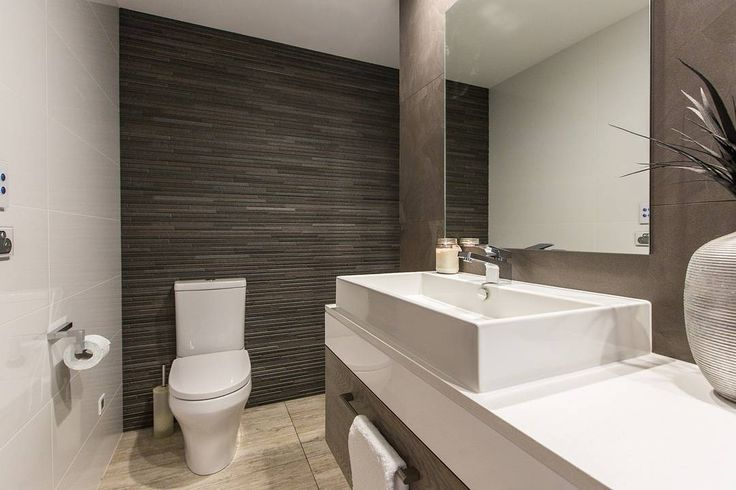 Use wood finishes or looks as a feature wall in the bathroom. Adds a bit of texture to a monochrome palette! A great bathroom by PJH Constructions