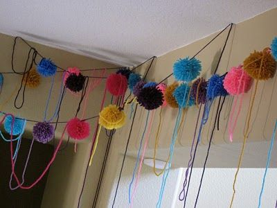 "What would a kitty cat party be without yarn? I couldn't get enough of these cute and colorful handmade poms. I strung them everywhere I could. It was a great way to bring in color to the party. I assure you that our cats had a great time ""helping"" me hang these!"