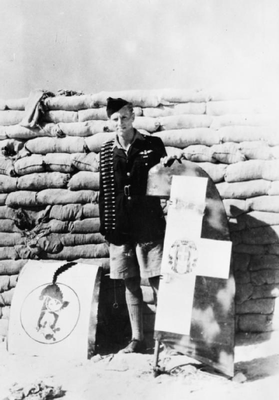 """A good day's work: Flight-Sergeant G F """"Screwball"""" Beurling of No. 249 Squadron RAF, standing by a sandbag revetment at Ta Kali, Malta, with the rudder and unit emblem cut from a crash-landed Macchi MC.202 of the Regia Aeronautica, one of four enemy aircraft which he shot down over Gozo on 27 July 1942."""