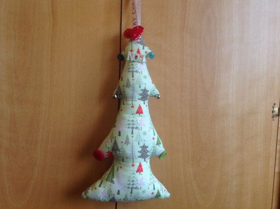 Christmas fabric tree. The fabric is lovely soft cotton, very tactile, in a light green colour, the fabric pattern has lots of small Christmas trees on.I have decorated it with little bells, and real buttons, and on the top is a little felt heart with little sliver beads, there is also a little Noel button attached. The whole item measures approximately 16 inches tall, and 7 inches at the widest part, and hangs from ribbon which has the words Merry Christmas printed on. Altogether a great…